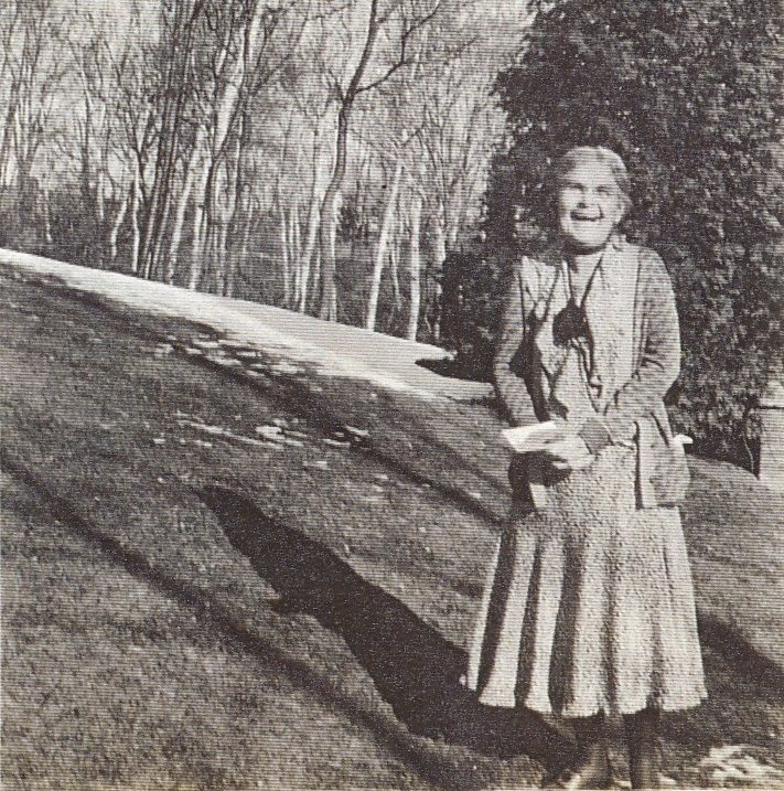 Elderly Clara is outside in spring with some snow left on the ground in the background. Her face is filled with joy as she laughs at whomever is behind the camera.