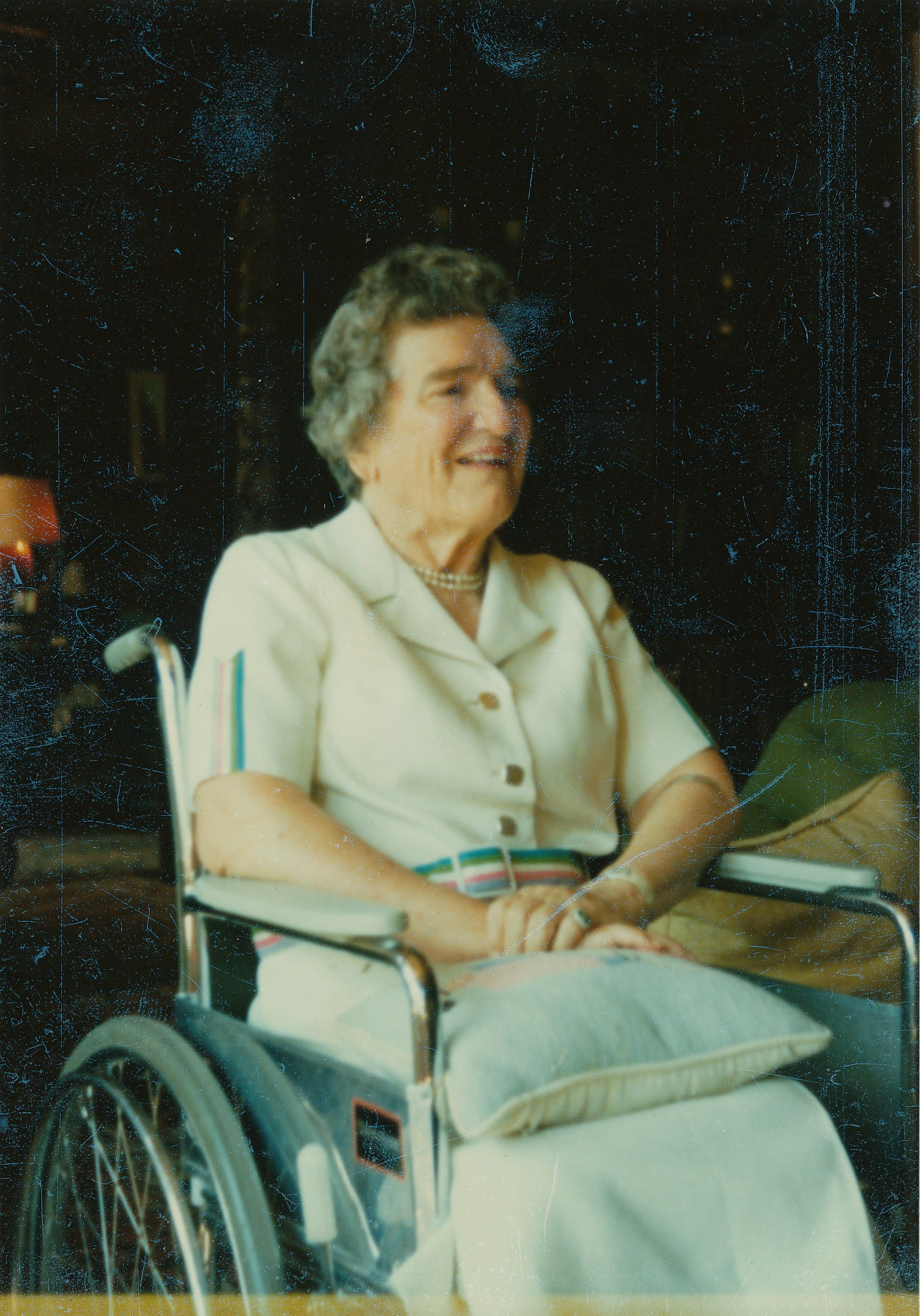Elisabeth smiles from her wheelchair on a sunny day.