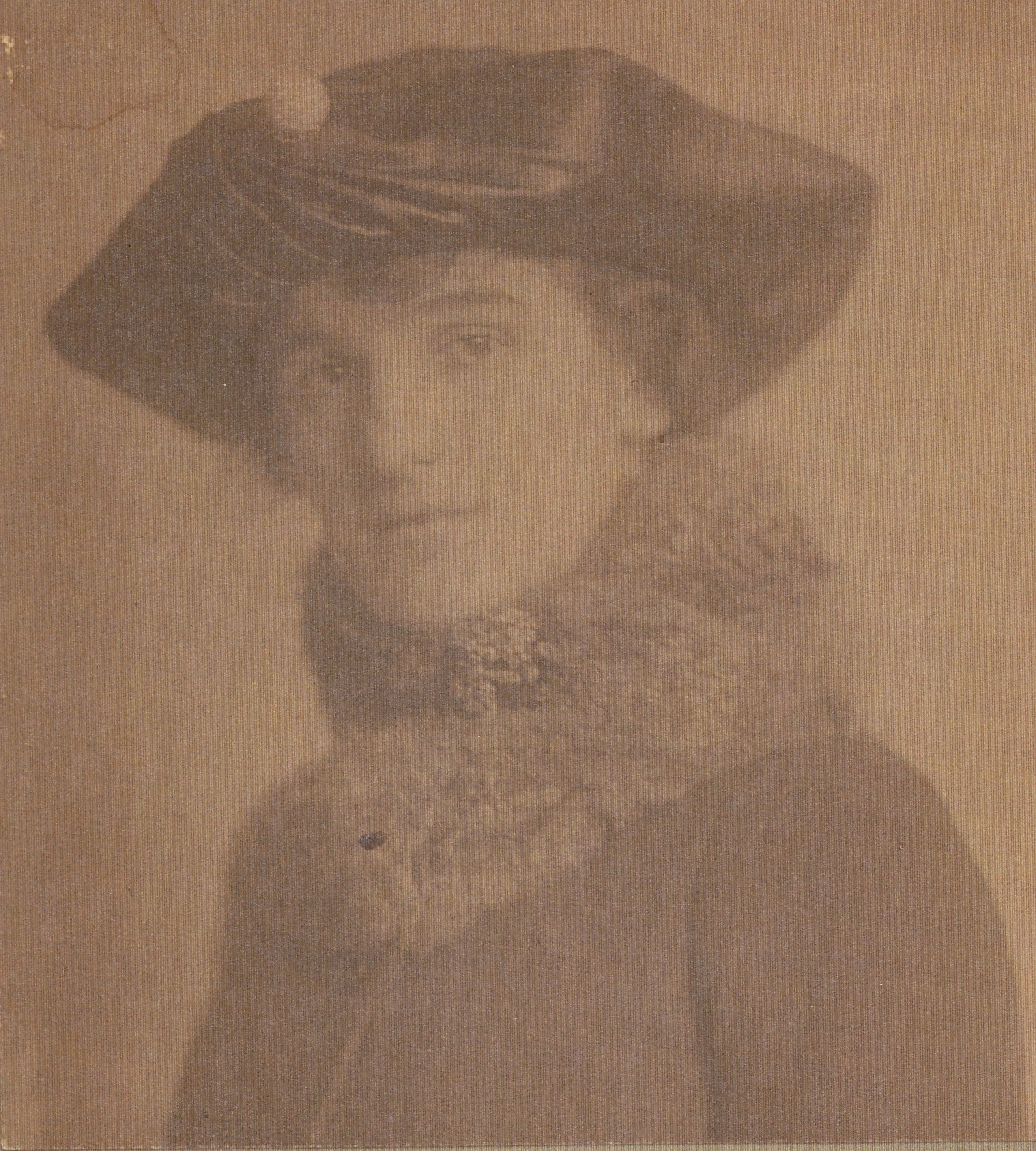 Elisabeth in a hat and coat looking at the camera.