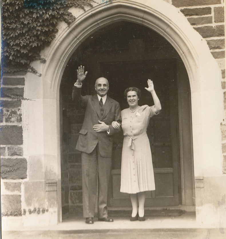 Harry and Marjorie wave to the camera as they stand in front of the Dudley mansion.