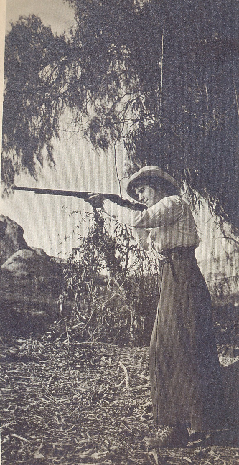 Young adult Helen Congdon stands on a rivebank and takes aim with a rifle. She is wearing a dress, boots, and a nice hat.