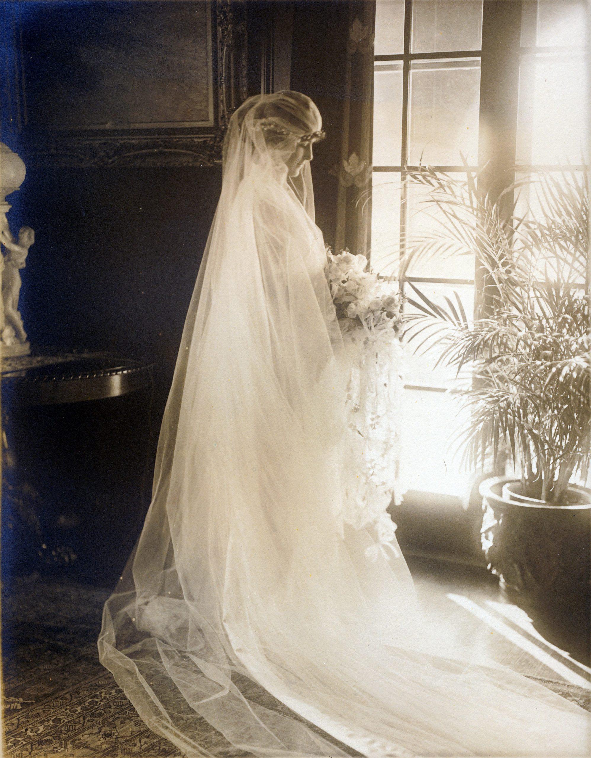 Helen Congdon looks out a window as her wedding dress train flirts across the floor.