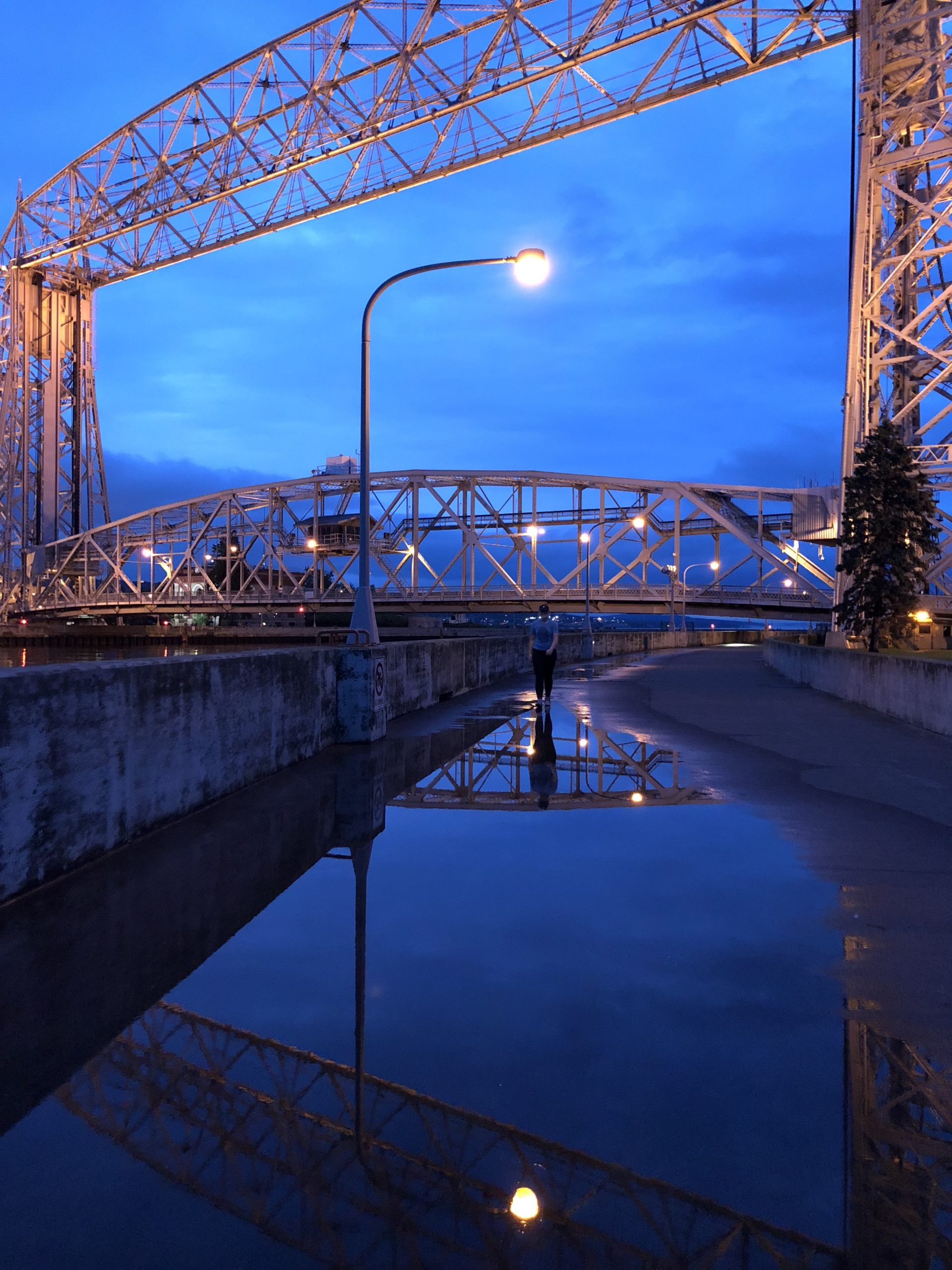 Lift bridge reflects in water on lakewalk.