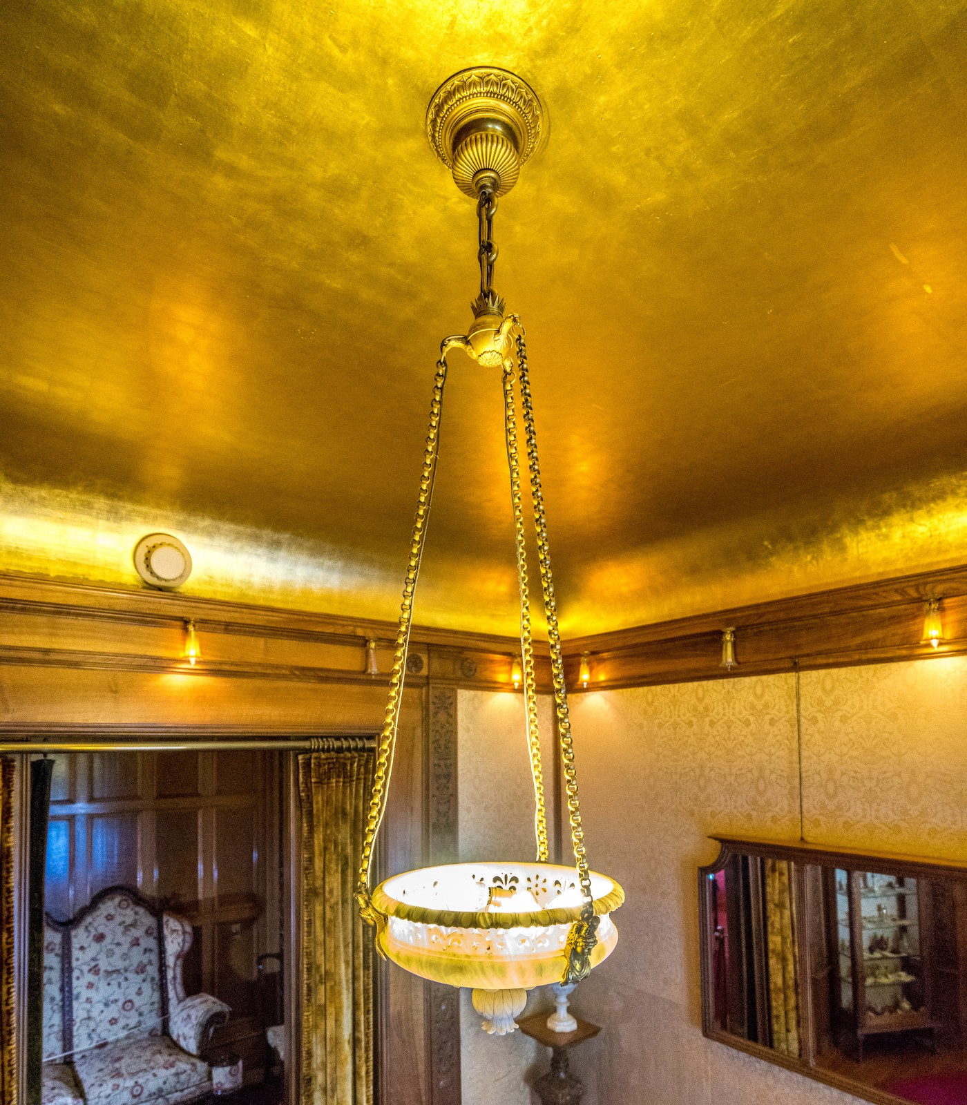The reception room's golden ceiling shines and is illuminated by the one of a kind hanging light fixture.