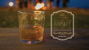 Whiskey glass in front of campfire.